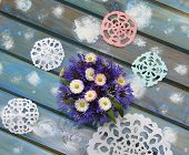 picture of christmas flower  - Lovely paper snowflakes and a bouquet of flowers on a blue wooden table a Christmas background - JPG