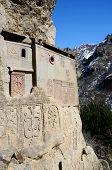 stock photo of armenia  - Cells of Geghard rock monastery with ancient khachkars  - JPG