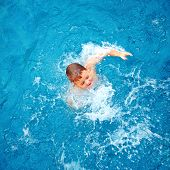 stock photo of wallow  - cute kid boy dabbling in pool water top view - JPG