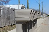 stock photo of mailbox  - Several Identical plastic mailboxes in a row at the edge of a street - JPG
