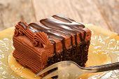 stock photo of chocolate fudge  - Chocolate sheet cake covered with chocolate icing and chocolate syrup on a plate with a fork - JPG