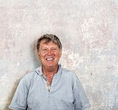 pic of rotten  - portrait of senior man in front of grungy old wall in a rotten house - JPG