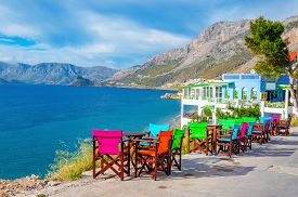 stock photo of greek-island  - Colorful wooden tables and chairs with view on sea bay on Greek Island - JPG