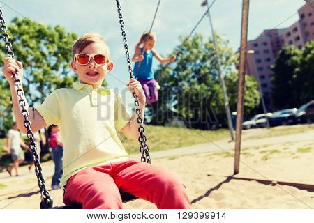 summer, childhood, leisure, friendship and people concept - two happy kids swinging on swing at chil