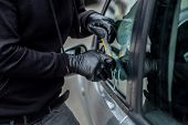 Car Thief Trying To Break Into A Car With A Screwdriver. poster