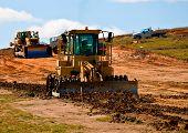 Earthmoving equipment ploughs a path
