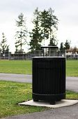 Black Trash Can In Park On Concrete Pad