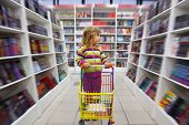 Little girl in bookshop, with cart for goods. There is one among racks.