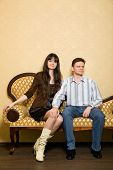 stock photo of scruple  - young beautiful woman and man sitting on sofa in room - JPG