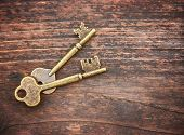 a set of old skeleton keys on a wooden background toned with a retro vintage filter instagram app or poster