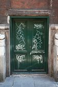 dirty, old, green, wooden doors, many white graffiti on doors