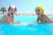 Two girls lie in  pool on skirting and laugh