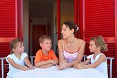 Three children and mother sit on  verandah  round table near doors and speak
