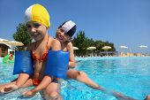 Three children play in  day-time in  large  pool under open-skies, underwater package shot