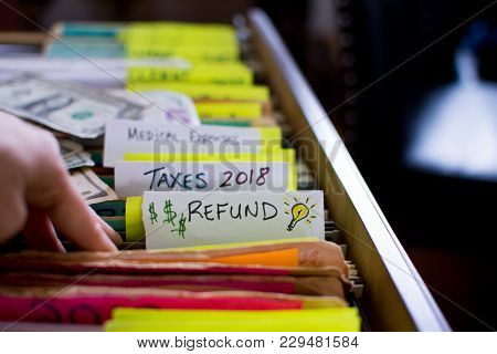 poster of Tax Refund Tax Filing For 2018 Tax Time,hand In Filing Cabinet Looking For Receipts And Deductions O
