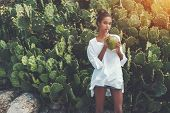 Young Sexy Brazilian Girl Is Standing In Front Of Green Hedge Of Cactuses And Drinking Coconut Water poster