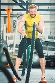 Full length low angle view of a handsome bodybuilder exercising with heavy battle ropes during inten poster