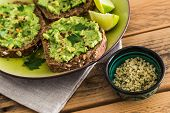 Mashed Avocado On Slices Of Toast With Seed Topping And Lime Slices poster