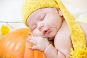 Portrait of a baby in yellow hat using pumpkin as a pillow