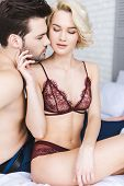 Sexy Young Woman In Lingerie Touching Handsome Boyfriend On Bed poster