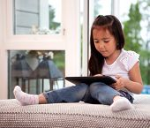 Portrait of a young child in a home interior engrossed in a game on a digital tablet