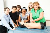 Group of students and their teacher, learning CPR in school.