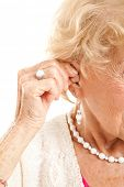 Closeup of a senior woman's hand inserting a hearing aid in her hear.