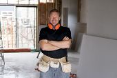Attractive And Confident Constructor Carpenter Or Builder Man With Ear Protection Gear Working Happy poster
