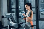 Young Athletic Sportswoman Drinking Water While Jogging On Treadmill At Gym poster