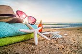 Sunglasses, Towels, Hat, Sun Block, Shells And Starfish On Sandy Beach poster