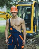 Muscular Builder In Hard Hat Wears Overalls. Sexy Man With Nude Torso Near Construction Equipment Or poster