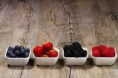 row of wild berries in bowls