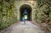 a male cyclist at MKT tunnel  on Katy Trail near Rocheport, Missouri. The Katy Trail is 237 mile bik poster