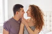 Portrait Of Affectionate Lovely Couple: Curly Woman And Brunet Male Look At Each Other`s Eyes With G poster