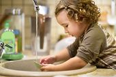 Сute Two-year-old Girl Is Washing Dishes In The Kitchen. Baby Helps The Parents. Nice Little Child L poster