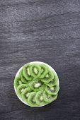 Fresh sliced kiwi on plate. Green Kiwi fruit slices on dark wooden background. Copy space. Kiwi cute poster