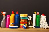Group Of Colorful Cleaning Products On Dark Background. Different Bottles, Sponges, Brushes And Mop  poster