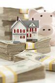 Casa pequena e cofrinho com pilhas de cem notas de dólar, isoladas em um fundo branco.