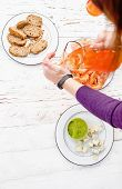 Woman Pouring Aperol Spritz Into A Glasses Over Dinner Table With Guacamole, Cheese And Bread On Rus poster