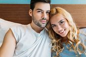 Affectionate Heterosexual Couple Looking At Camera In Bed poster
