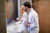 Affectionate Couple Looking At Mirror In White Bathrobes In Bathroom poster