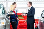 Couple buying car at dealership and consulting salesman poster