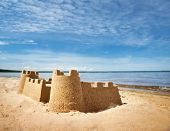 Sandcastle On The Sea In Summertime. Seashore On Beautiful Day. Sand On The Beach And Blue Water poster