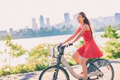 City bike young woman biking riding bicycle in street outdoors in summer with city skyline. Happy mu poster