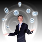 stock photo of juggling  - businessman in blue suit standing and juggling business symbols - JPG