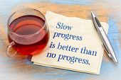 Slow progress is better than no progress inspirational note - handwriting on a napkin with a cup of  poster