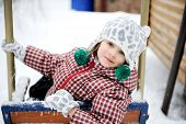 Adorable Child Girl Enjoys Seesaw In Winter