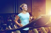 sport, fitness, lifestyle, technology and people concept - smiling woman exercising on treadmill in  poster