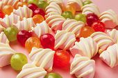 Closeup Of Heap Of Marshmallows And Colourful Sweets On Pink Background. Confectionery Store Adverti poster