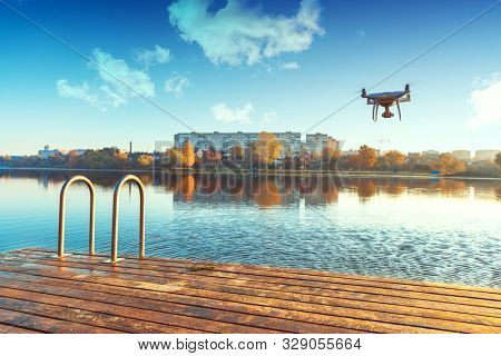 poster of Drone copter with digital camera, blur river on background